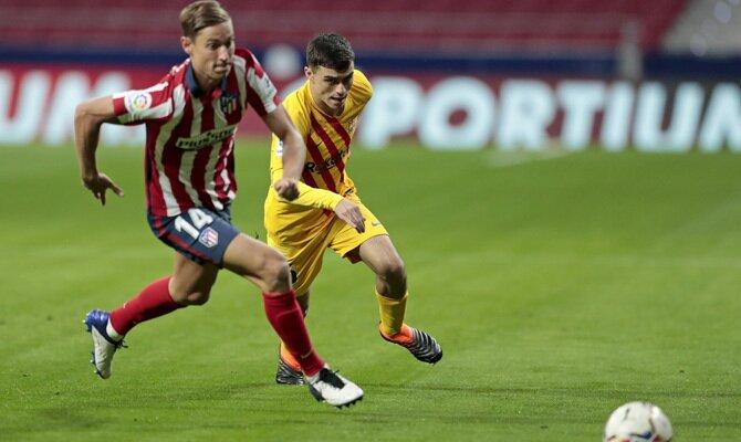 Pedri, a la derecha, persigue a Marcos Llorente. Cuotas y picks Barcelona vs Atlético de LaLiga