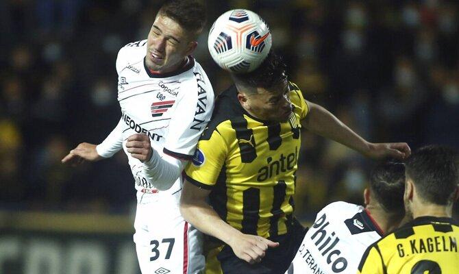 Bissoli y Rodríguez pelean por un balón aéreo. Cuotas y picks Athletico Paranaense vs Peñarol.